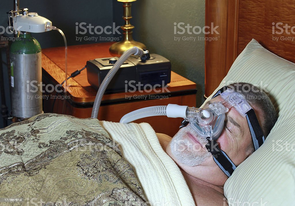 Senior Man Sleeps with CPAP and Oxygen stock photo