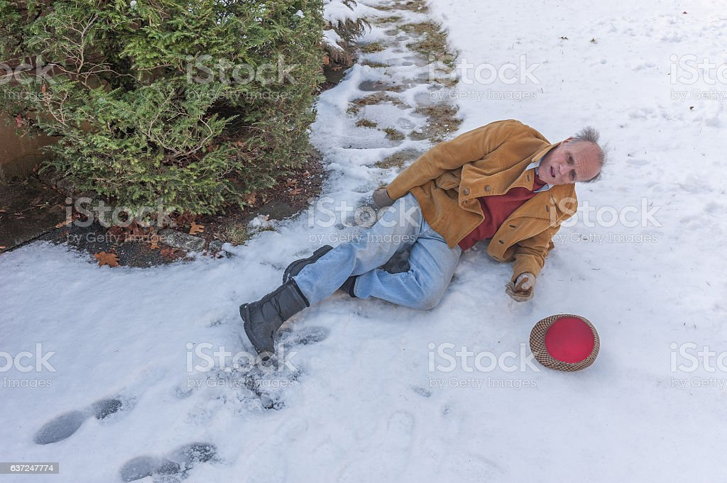 Senior man slipping on ice on his walkway stock photo