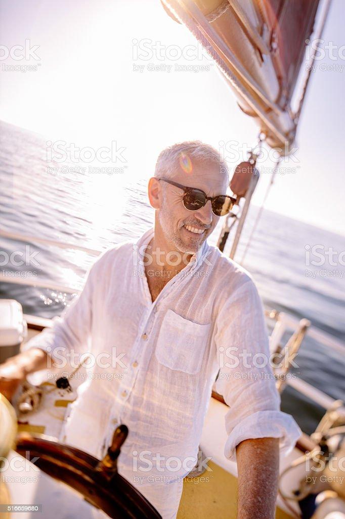 Senior man smiling as boat captain of his recreational boat stock photo