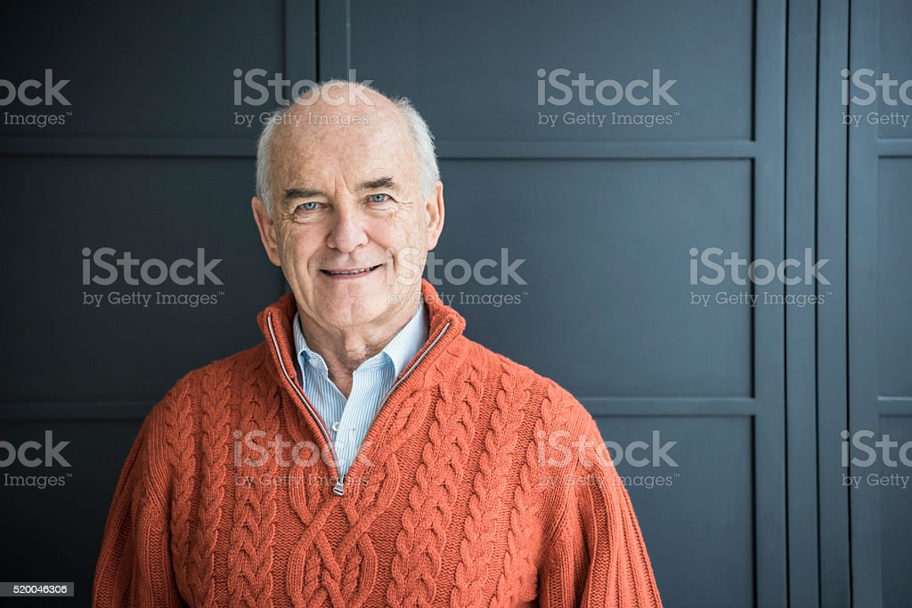 Senior man smiling, wearing orange sweater stock photo