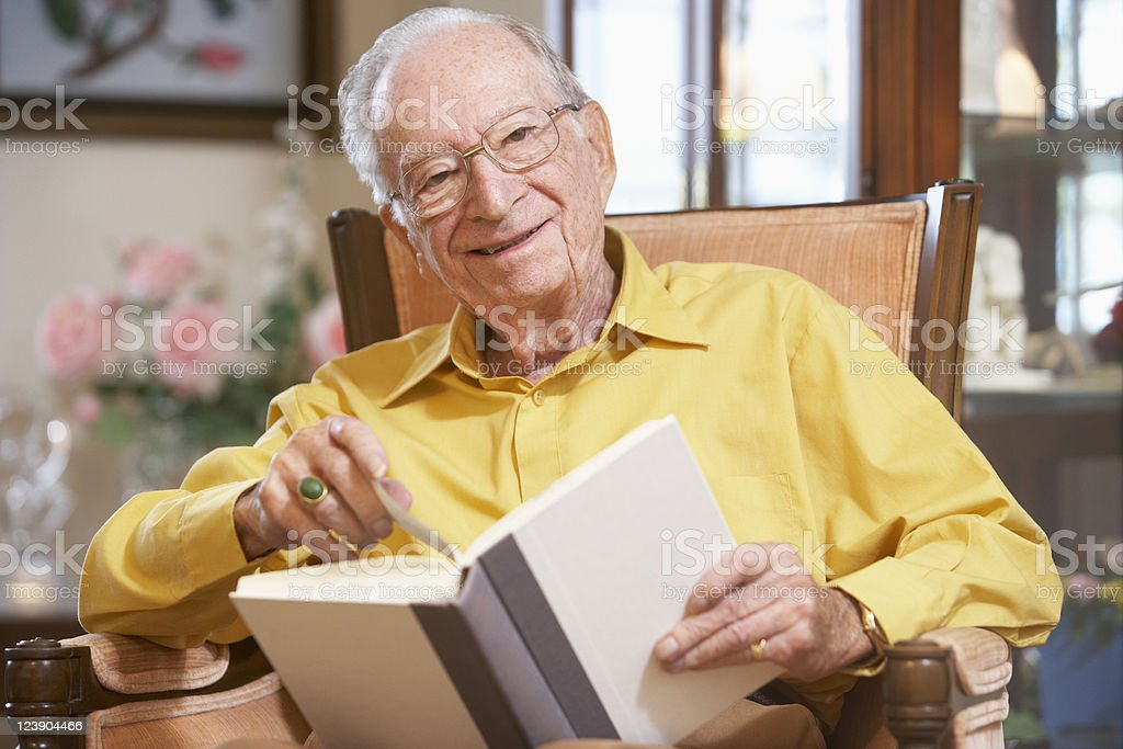 A senior man smiling while holding a book royalty-free stock photo