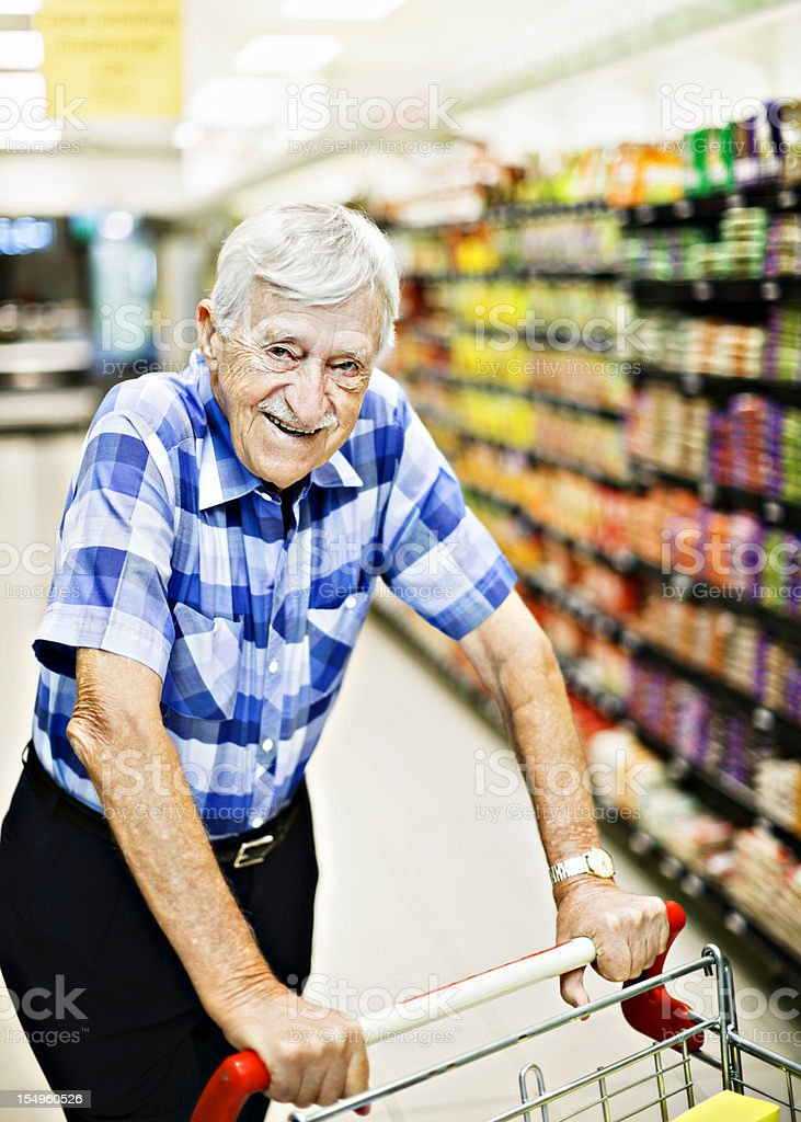 Senior man smilingly pushing shopping cart in supermarket stock photo