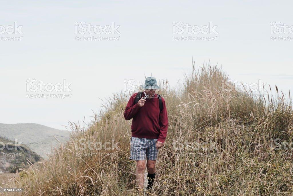 A Senior Man Smokes his Pipe whilst Walking stock photo