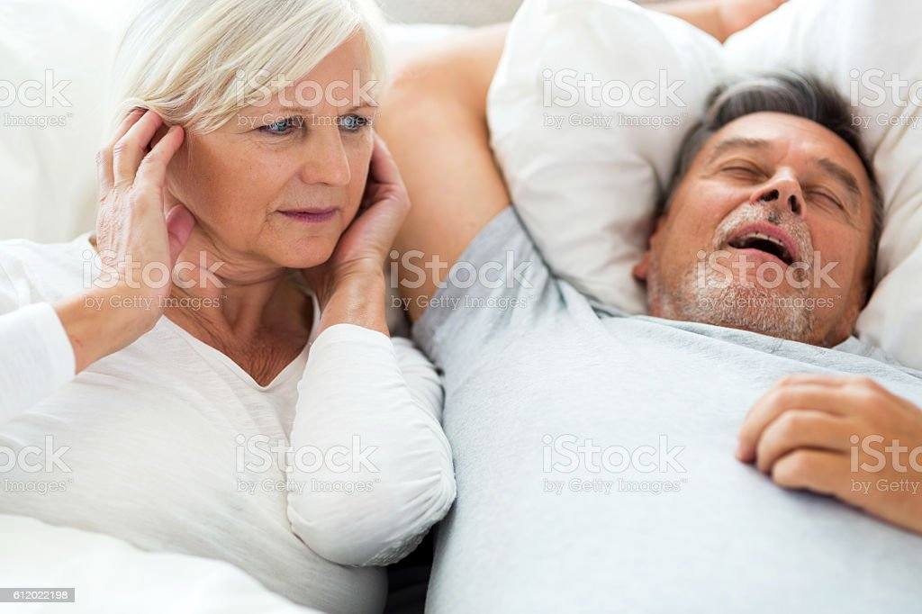 Senior man snoring and woman covering ears stock photo