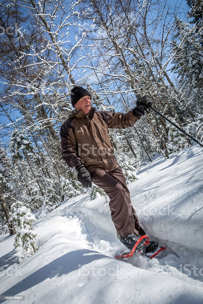 Senior Man Snowshoeing in Winter Forest stock photo