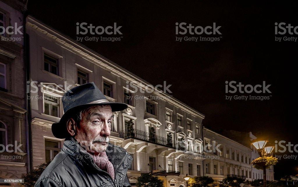 Senior man spy concept in city at night stock photo