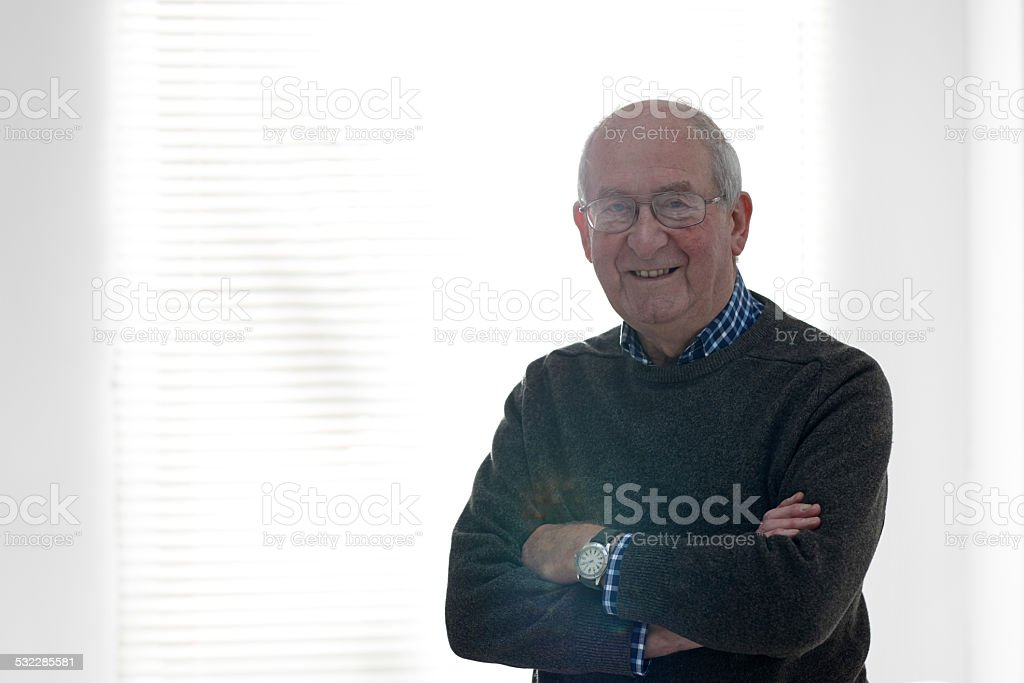 Senior man standing by a window looking happy stock photo