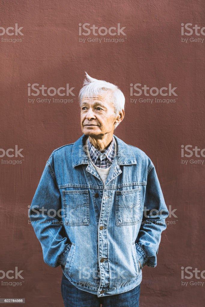 Senior man standing hands in pockets stock photo