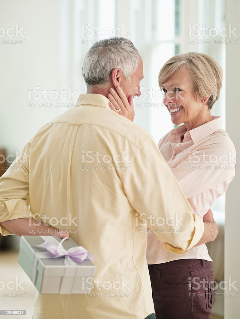 Senior man standing in front of mature woman, hiding present behind back royalty-free stock photo