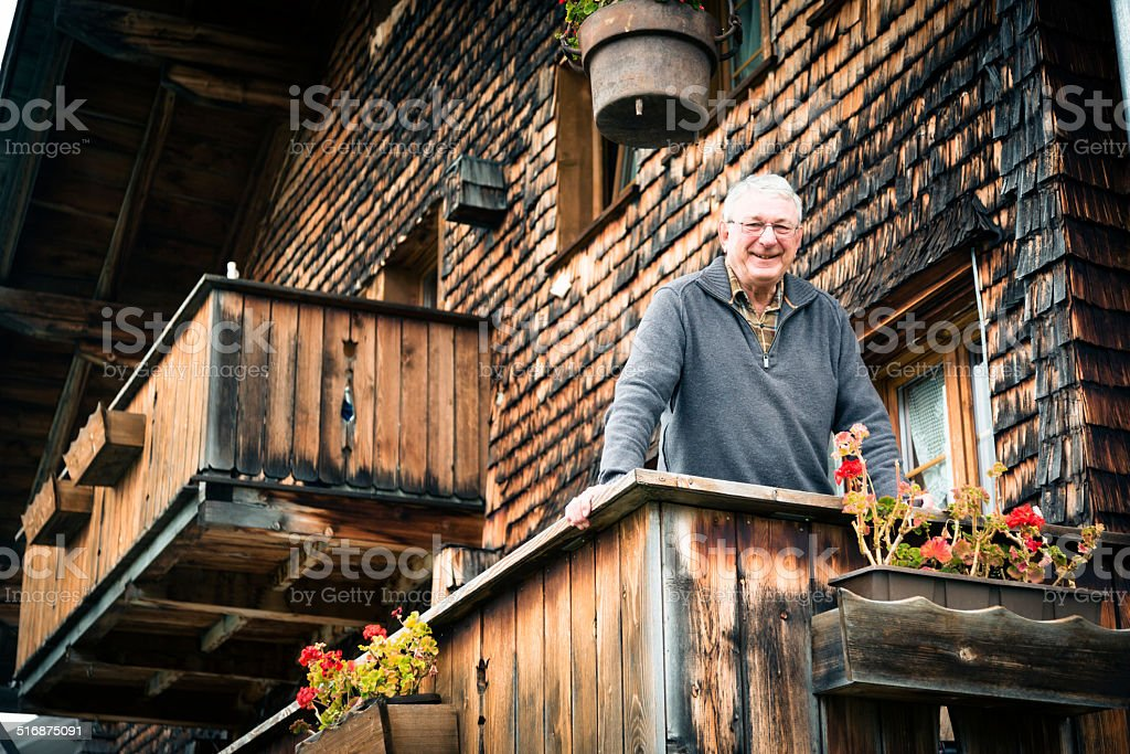 senior man standing on balcony stock photo