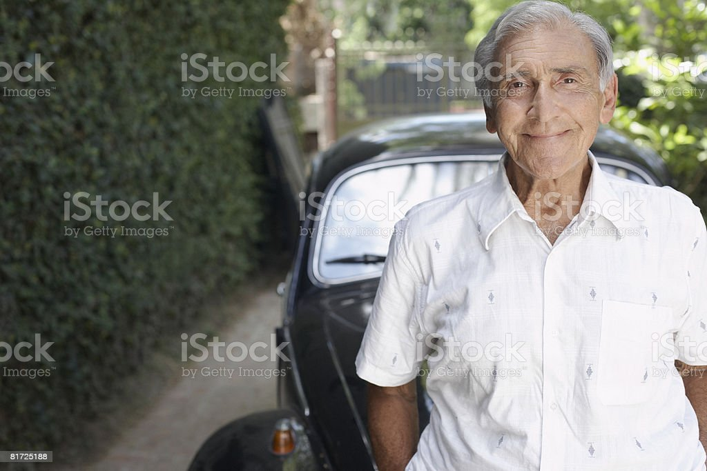 Senior man standing outdoors by car smiling royalty-free stock photo