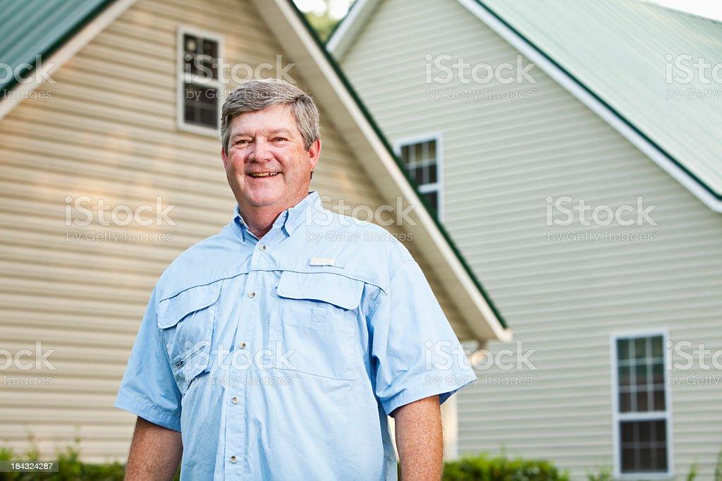 Senior man standing outside home stock photo