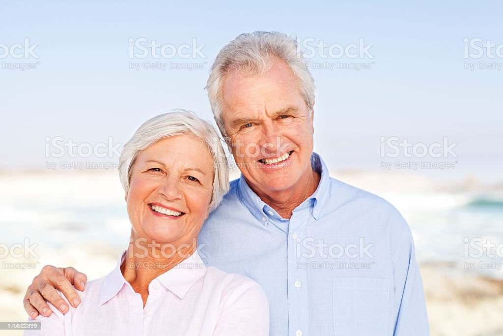Senior Man Standing With Arm Around Woman At Beach royalty-free stock photo