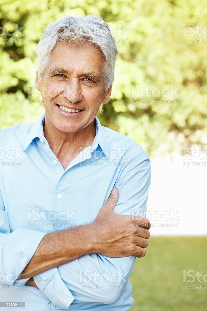 Senior man standing with arms crossed outdoors royalty-free stock photo