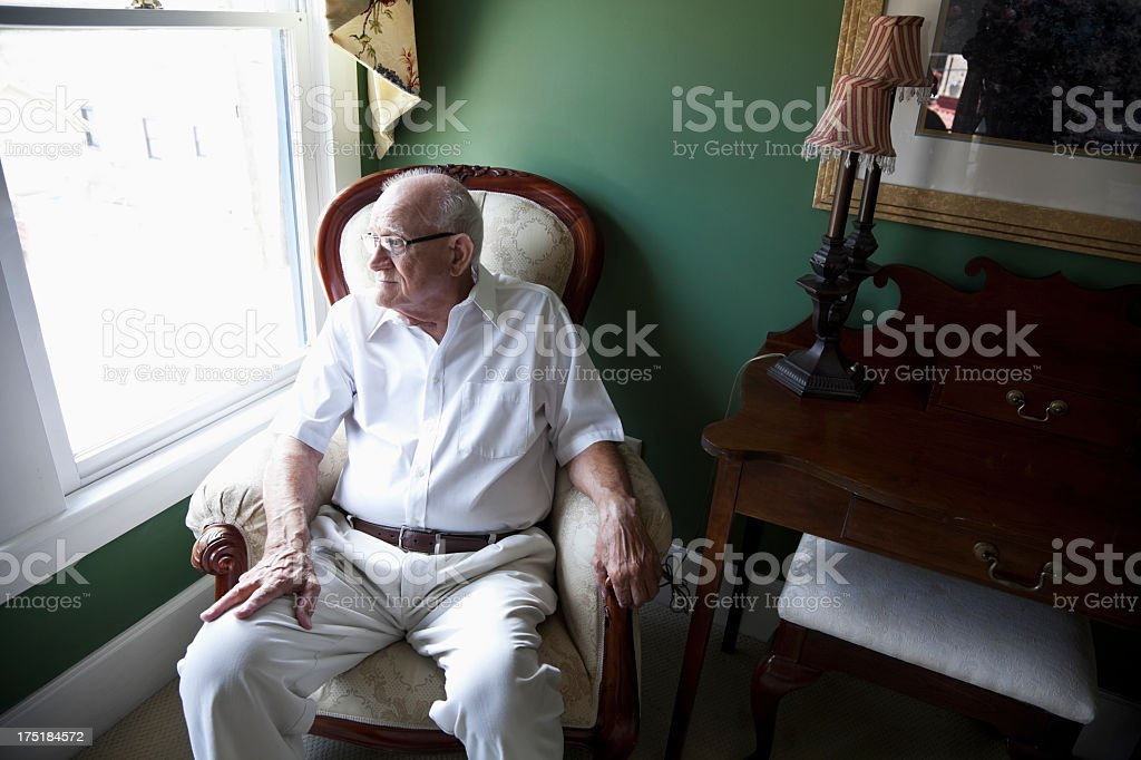Senior man staring out a window royalty-free stock photo