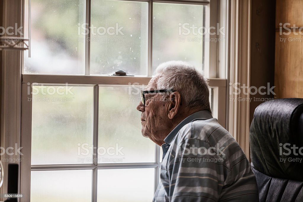Senior Man Staring Through Grungy Window stock photo