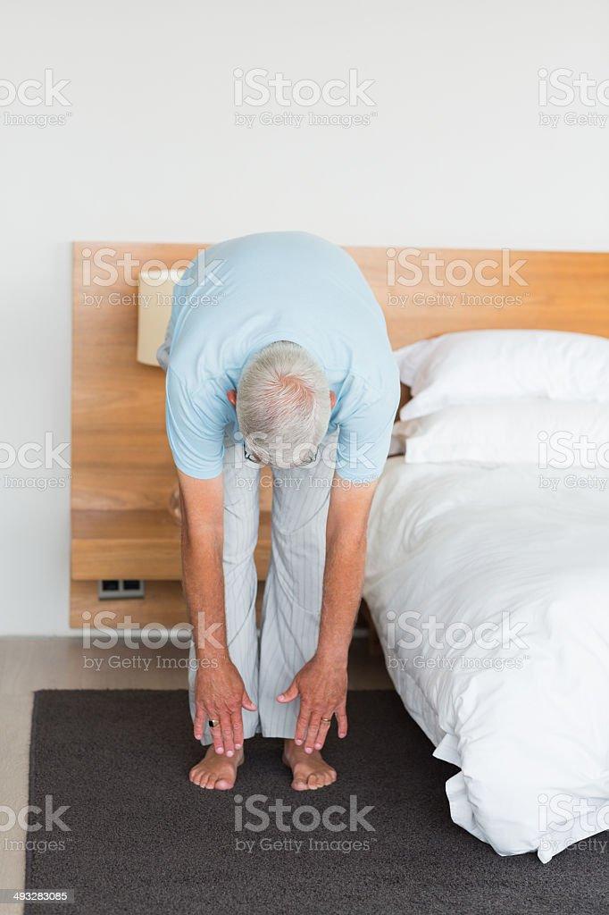 Senior man stretching in bedroom stock photo