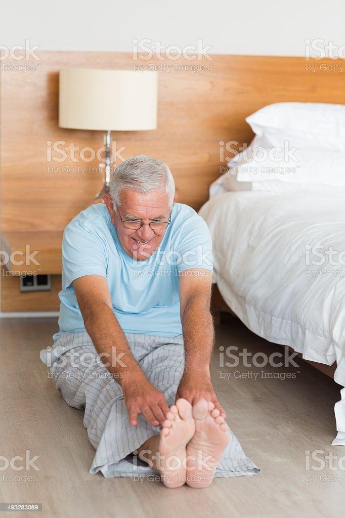 Senior man stretching legs in bedroom stock photo
