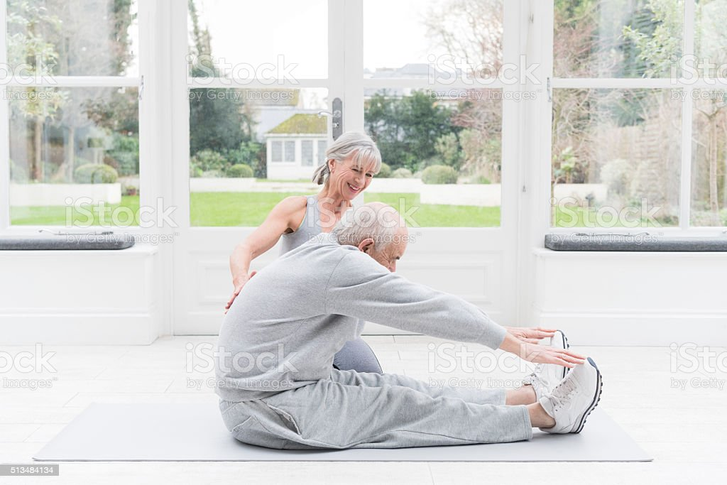 Senior man stretching legs with female fitness instructor watching stock photo