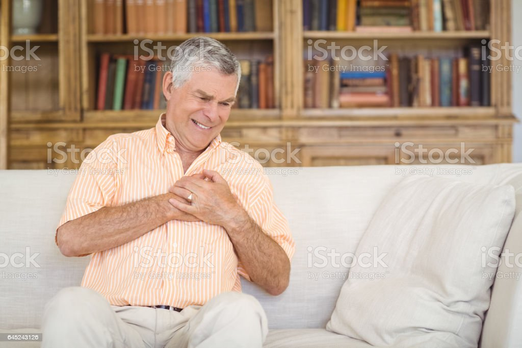 Senior man suffering from chest pain in living room stock photo
