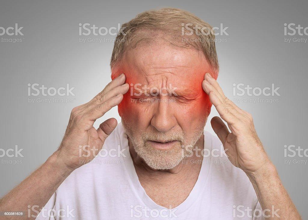 senior man suffering from headache hands on head stock photo