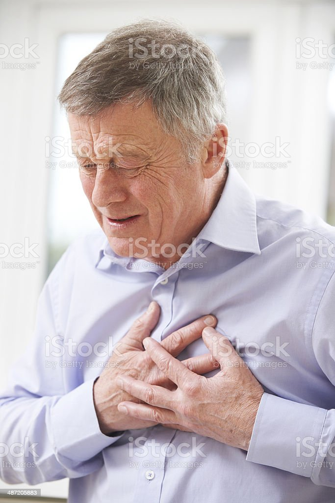 Senior Man Suffering Heart Attack At Home stock photo