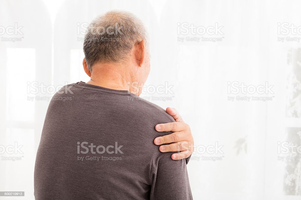 senior man suffering in shoulder pain stock photo