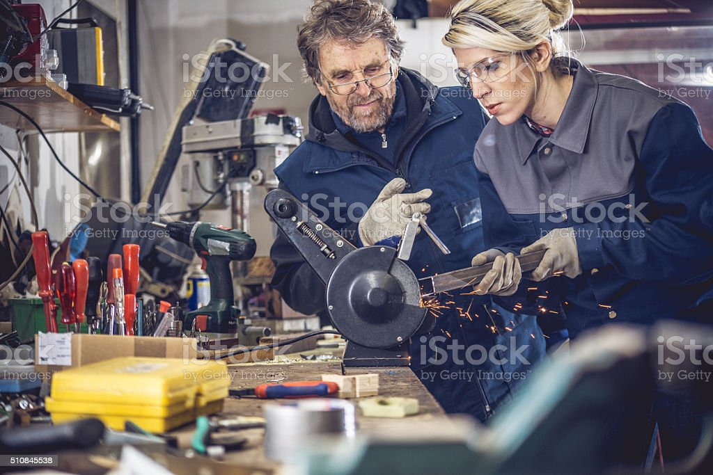 Senior Man Supervising Young Woman While Grinding Metal in Garage stock photo