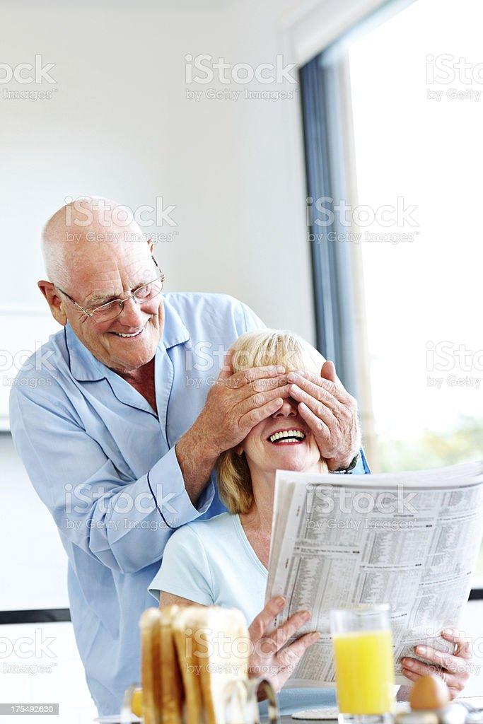 Senior man surprising his wife in morning royalty-free stock photo