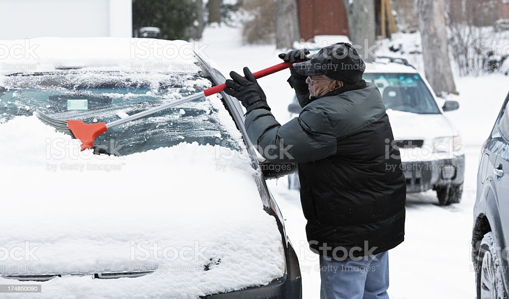 Senior Man Sweeping Snow From Car Windshield stock photo