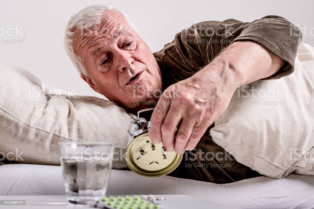Senior man switching off the alarm clock stock photo