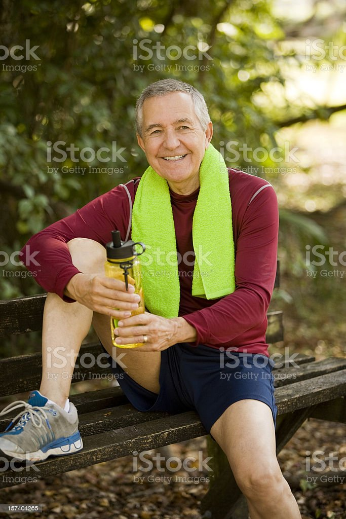 Senior man taking a break after a long run in the park royalty-free stock photo