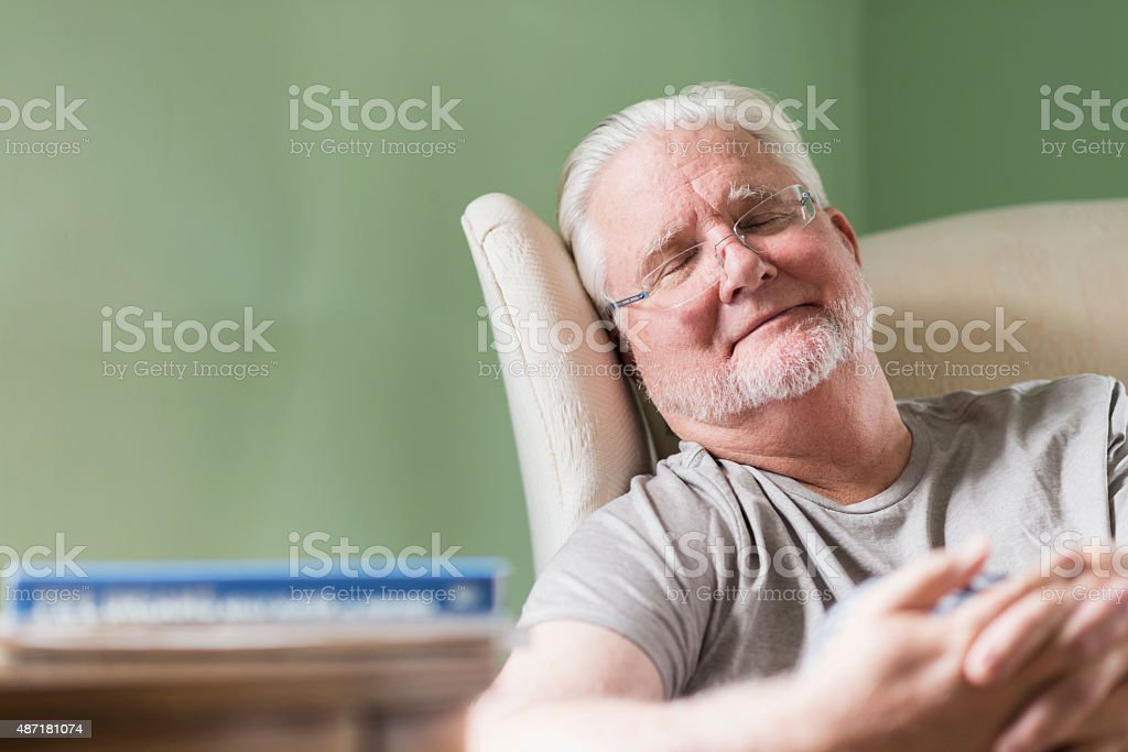 Senior man taking a nap in a chair stock photo