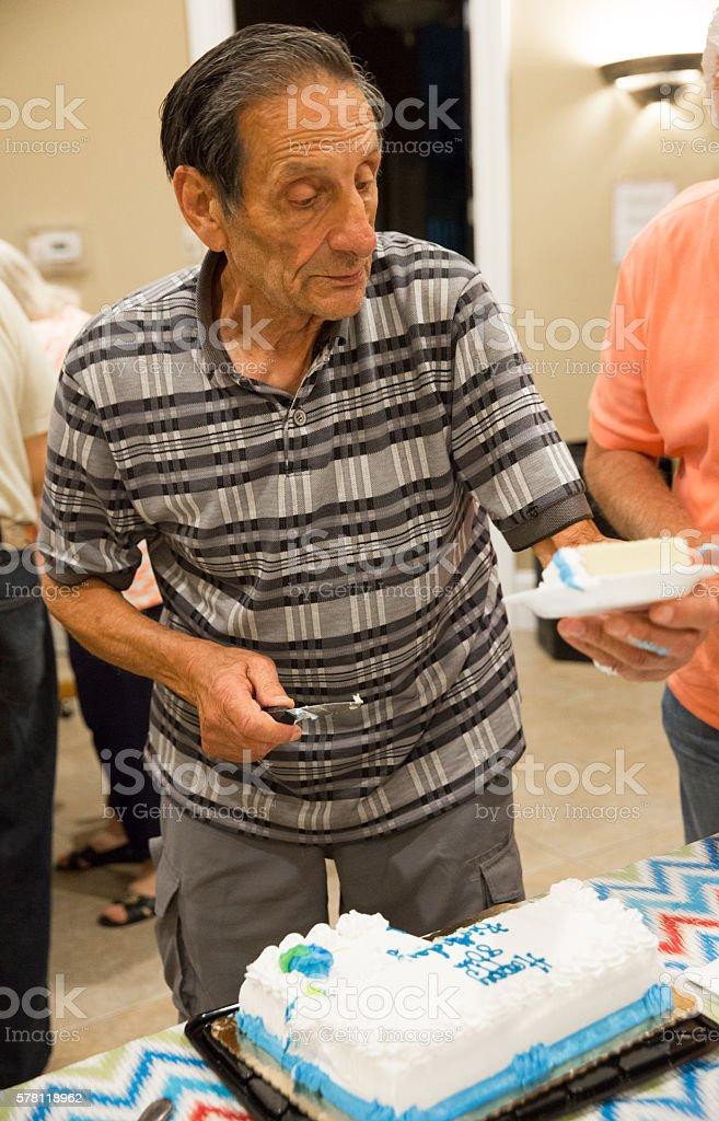 Senior man taking a piece of birthday cake at party stock photo