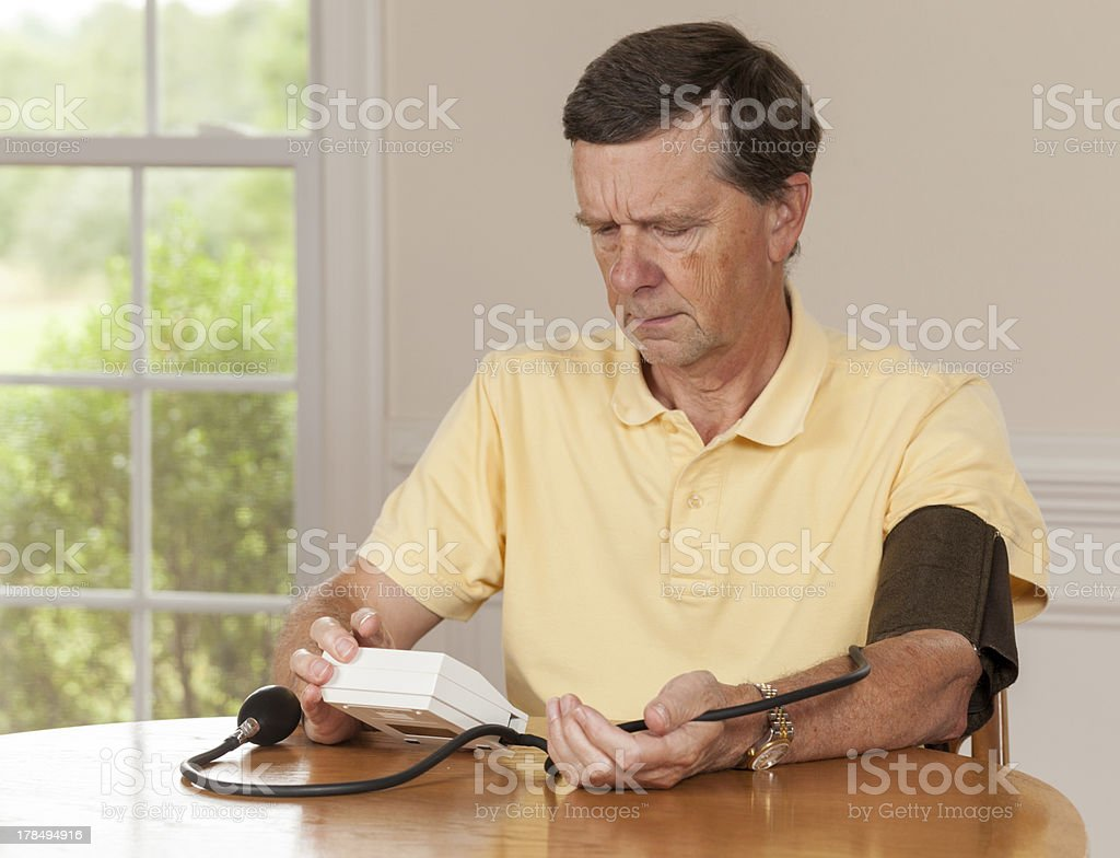 Senior man taking blood pressure at home royalty-free stock photo