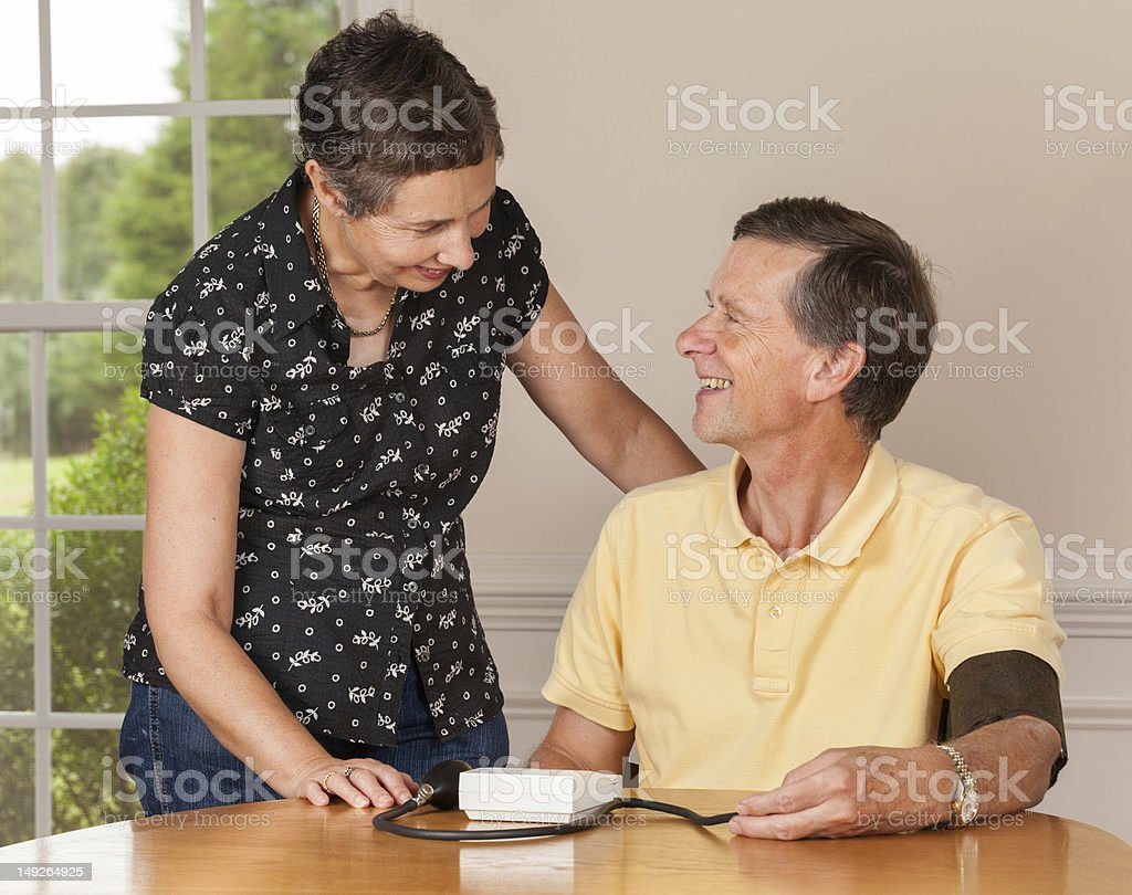 Senior man taking blood pressure with wife royalty-free stock photo
