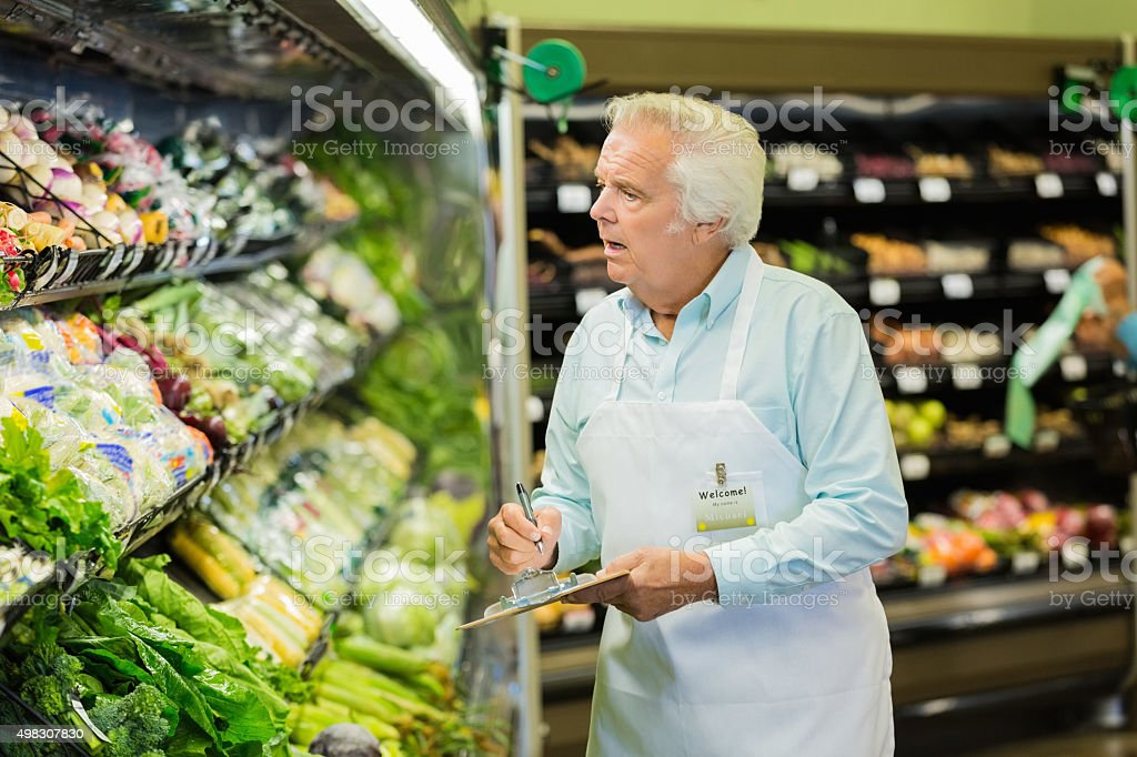 Senior man taking inventory in local grocery store or supermarket stock photo