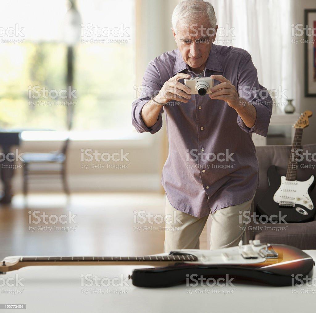 Senior man taking photograph of guitar stock photo