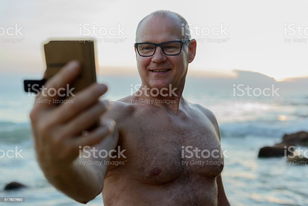 Senior man taking selfie at beach stock photo