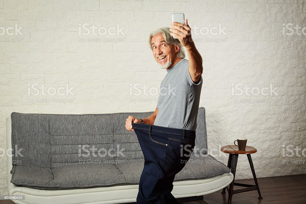 Senior man taking selfie, showing her weight loss stock photo