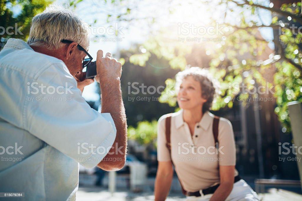 Senior man taking vacation photographs of his wife stock photo