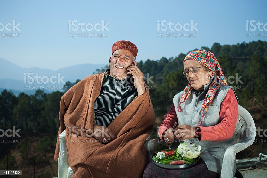 Senior man talking on phone and his wife cutting vegetables. stock photo