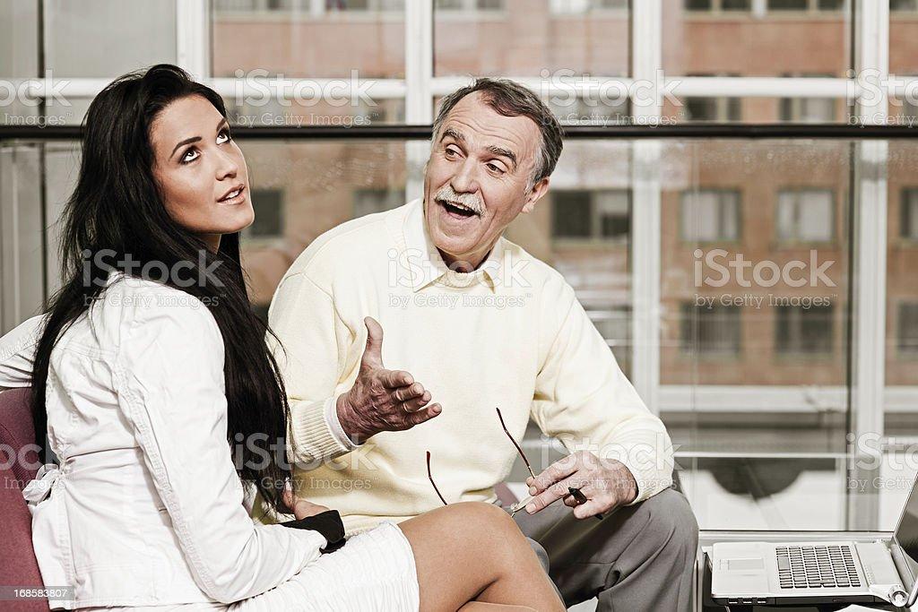 Senior man talking to a young woman stock photo