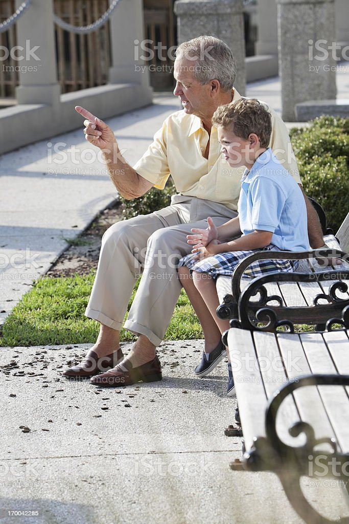Senior man talking to grandson on park bench stock photo
