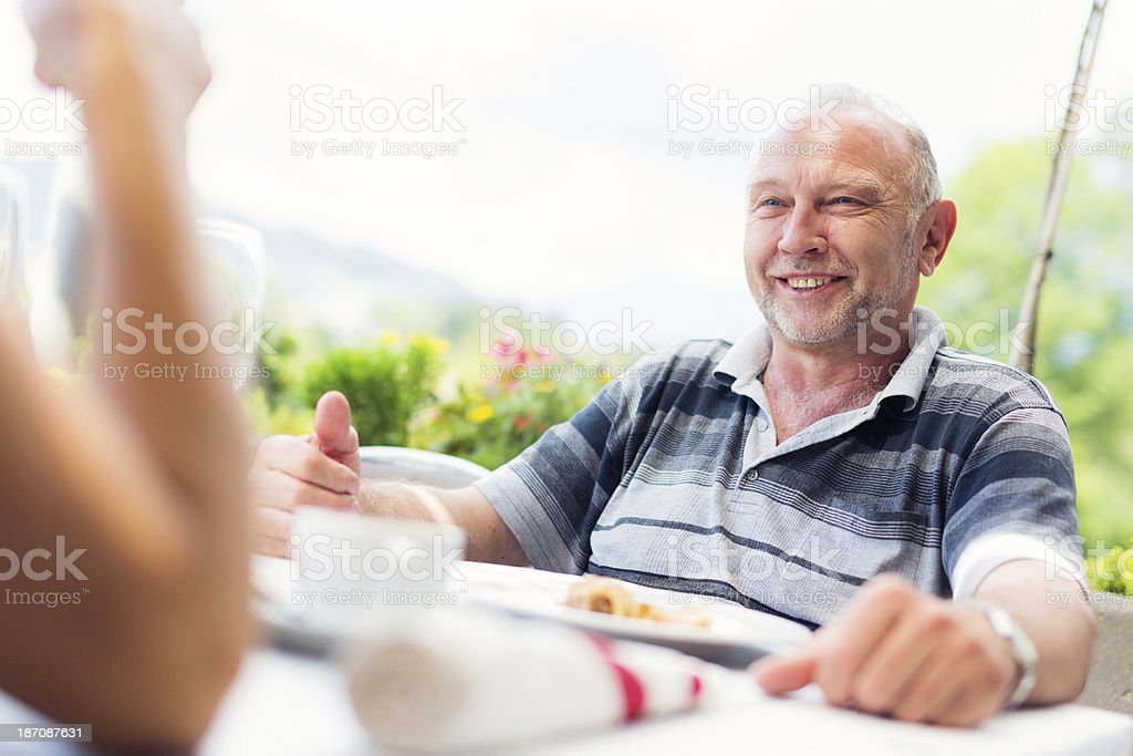 senior man talking to his wife at a restaurant royalty-free stock photo