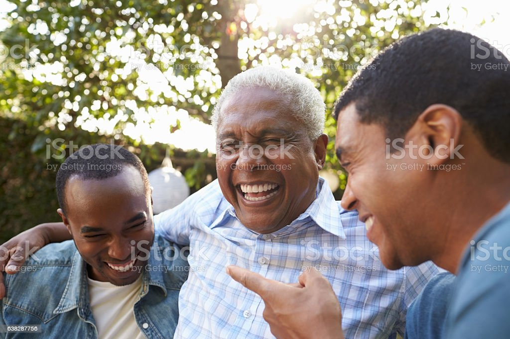 Senior man talking with his adult sons in garden, stock photo