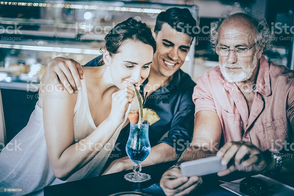 Senior Man Talking with Teenage Couple in Patisserie stock photo