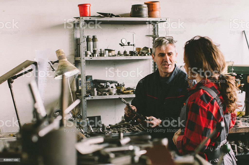 Senior man teaching her how to use lathe... stock photo