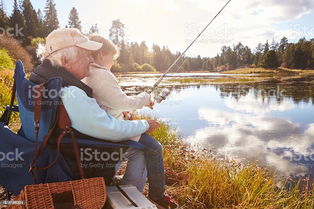 Senior man teaching his grandson to fish at a lake stock photo
