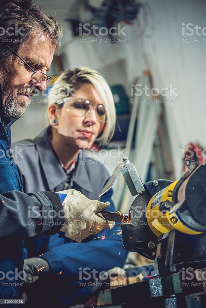 Senior Man Teaching Young Woman How to Grind Metal stock photo